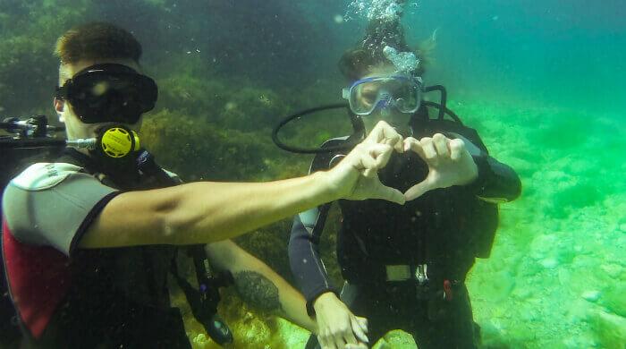 Влюбленные показывают руками сердечко во время дайвинга на Чаше Любви (Тарханкут, Крым) Фото